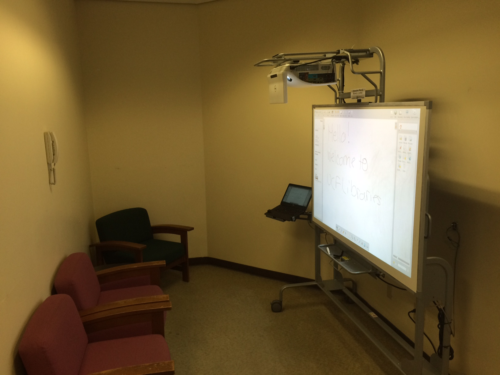 An interactive whiteboard is placed at the center of a study room