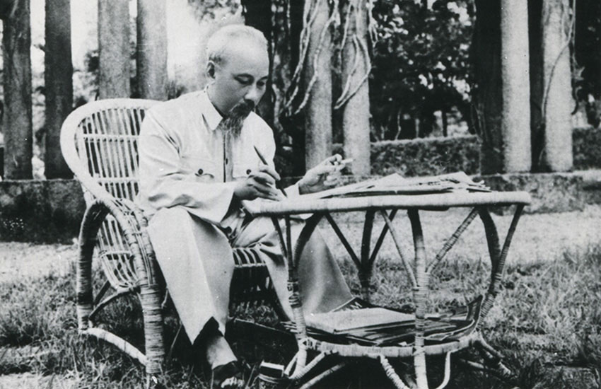 Hồ Chí Minh (1890-1969) sitting at a table in the gardens of the Presidential Palace, Hanoi, Viet Nam, 1957.
